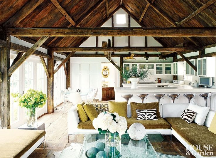 In the living room of a Connecticut farmhouse, sleek, low-slung furnishings, a light palette, and large windows are juxtaposed with the dark rustic ceiling beams. #HouseandGarden