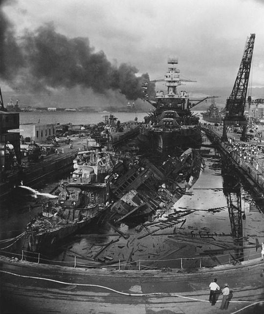 The wrecked destroyers USS Downes (DD-375) and USS Cassin (DD-372) in Drydock One at the Pearl Harbor Navy Yard, soon after the Japanese air attack. Cassin has capsized against Downes. USS Pennsylvania (BB-38) is astern, occupying the rest of the drydock. The torpedo-damaged cruiser USS Helena (CL-50) is in the right distance, beyond the crane. Visible in the center distance is the capsized USS Oklahoma (BB-37), with USS Maryland (BB-46) alongside. The smoke is from the USS Arizona (BB-39).
