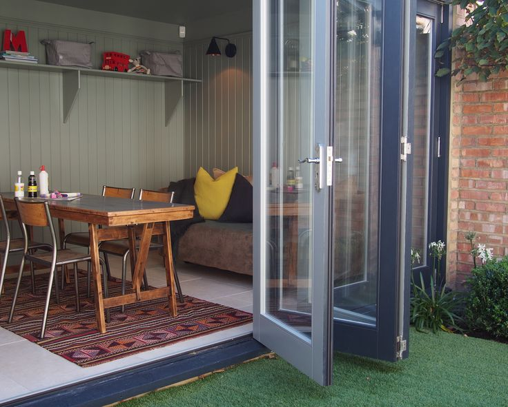 Shed turned into a playroom: Bi-fold doors opening onto the garden, Wall colour in Pigeon by Farrow & Ball