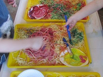 Spaghetti Sensory Play... MAKnote: If you drop wet spaghetti strands on a piece of waxed paper and let them dry, you can peel them off later and hang them from yarn on a paper clip... very funny mobiles!