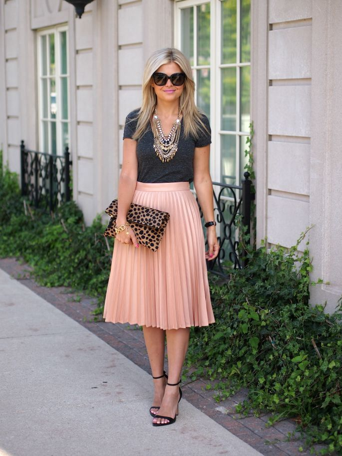 Love the simple black top with the pink/coral pleated midi and simple black sandals. The oversized necklace adds volume to the look.
