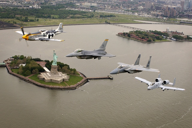 """P-51 """"Mustang"""", F-16 """"Falcon"""", F-15 """"Eagle"""" and A-10 """"Thunderbolt II"""" in formation over the Statue of Liberty."""