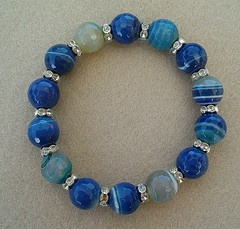 Bracelet made of 14 mm faceted dark blue agate and silver plated rhinestone spacer beads.