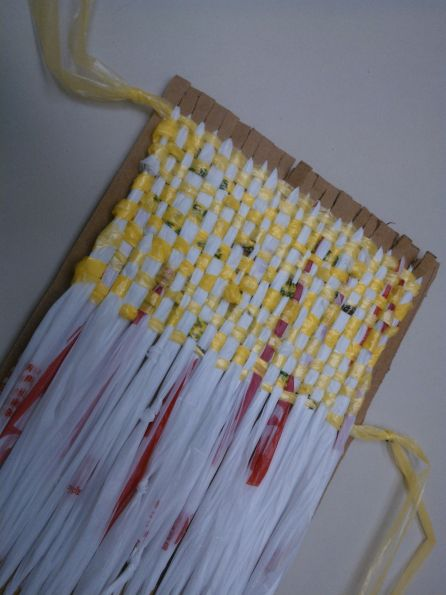 "Make a cardboard loom to weave using ""plarn"" (plastic bags cut into strips)"