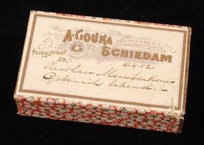 """Rechthoekig kartonnen pillendoos """"A. Gouka, Apotheker, Schiedam"""" met handgeschreven opschrift en gebloemde zijkant."""