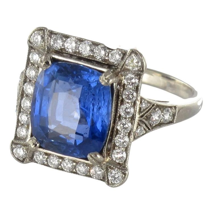 French Ceylon Sapphire Diamond Gold Ring. 18K white gold ring, eagle head hallmark.  This splendid rectangular shaped sapphire and white gold ring boasts a cushion cut Ceylan Blue sapphire held by 4 claws surrounded by brilliant cut diamonds of which the 4 corner ones are surmounted by a geometric decoration. The shoulders of the ring are set on both sides with diamonds. The setting is of perforated arabesques.