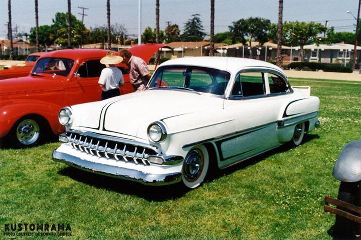 Here's another one of Howard Gribble's photos from the 1995 Sultans of Long Beach hot rod and custom car show held on the athletic field at Millikan High School in Long Beach California.  A mildly restyled and scalloped 1954 Chevrolet custom! Extra teeth gives the front end a heavier appearance. It has been shaved for door handles and hood chrome. Dodge Lancer hubcaps is used to wrap up the late 1950s look. A great custom for 1995!
