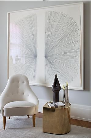 a large framed wall art print into this gray colored room with a white arm sofa chair and gold polished cabinet and some monochrome accessories on the
