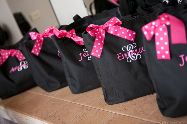 Hot pink polka dot bows on black embroidered weekend bags for the bridesmaids. Wedding Planning by MuseEvents.com