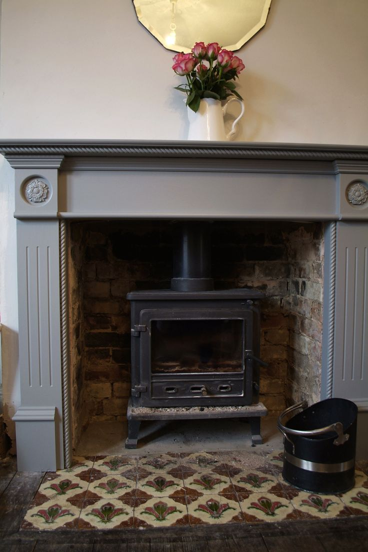 Farrow & ball manor house grey painted surround. Wood burner with exposed brick inside the void.