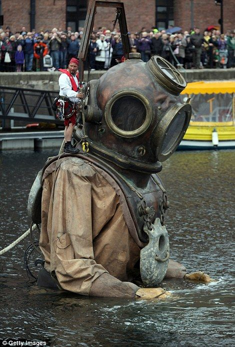 A giant deep sea diver, the uncle of the little giant girl, emerges from the Albert Dock in Liverpool