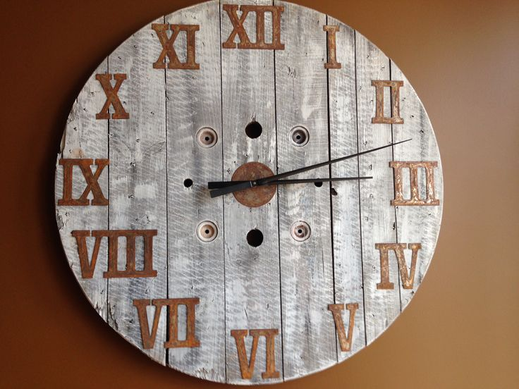 Large wood spool clock with off white milk paint and rusted metal Roman numerals.