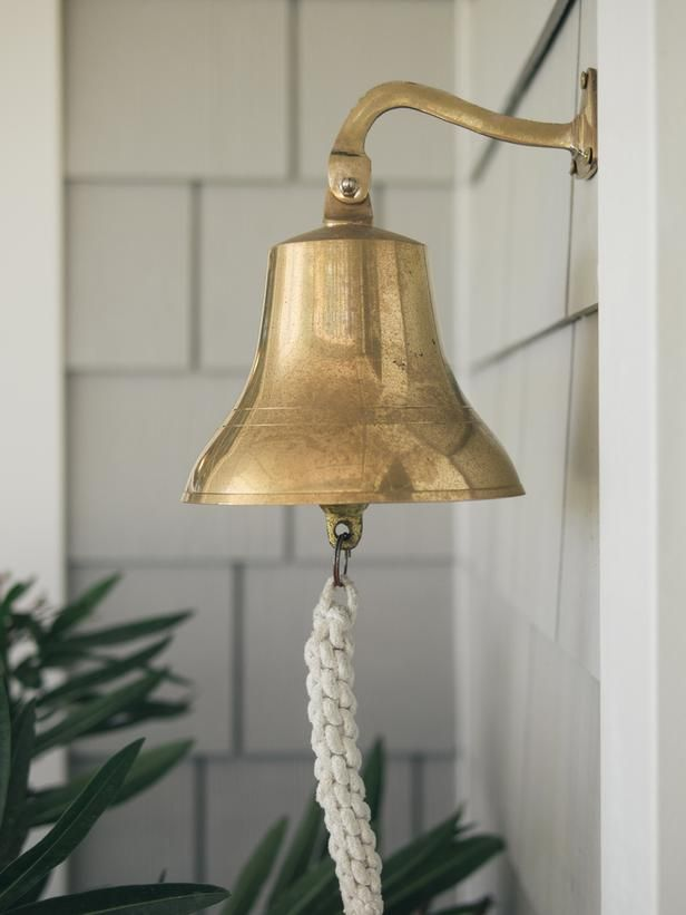 Blog Cabin 2013: East Entry Pictures: A hanging brass ship's bell stands in place of a traditional doorbell or knocker. The decorative door hardware, selected by online voters, offers a nod to the Core Sound maritime traditions of boat-building and commercial fishing. From DIYnetwork.com