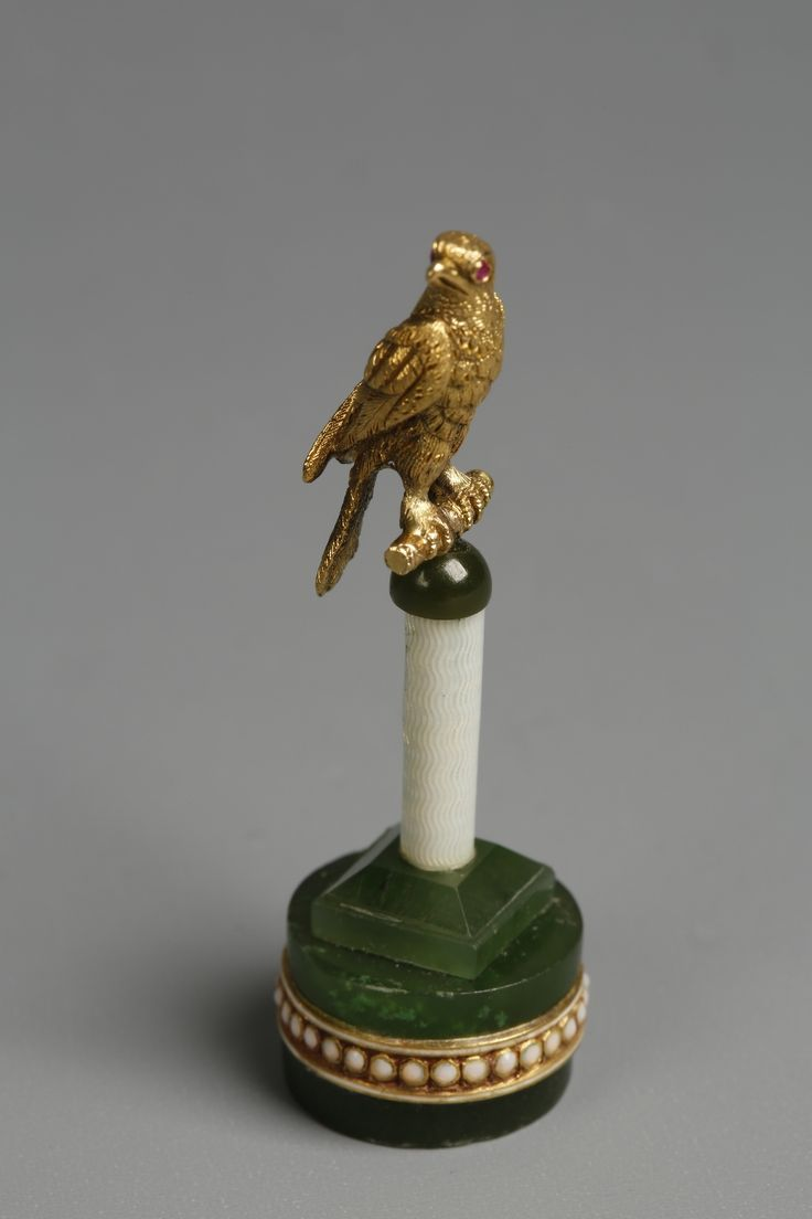 FABERGE: A NEPHRITE ENAMEL AND GOLD MINIATURE EAGLE ORNAMENT~ The bird has ruby coloured eyes on a white enamel column and faceted Nephrite base, with enamel banding and Faberge markings.