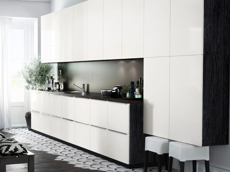 Modern IKEA kitchen with black brown cabinets, high gloss white cabiet doors and dark worktops