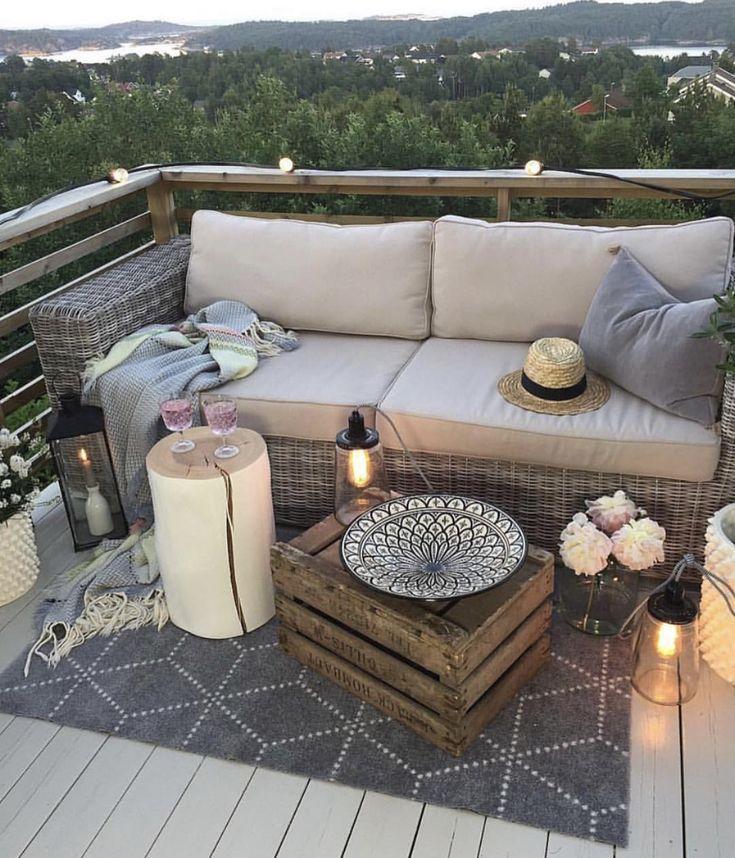 Terrasse mit Rattanmöbeln, grauem Teppich, Kerzen, grauen Akzenten