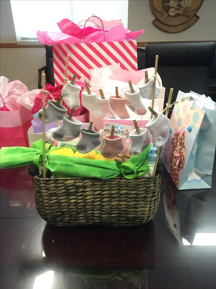 Unique Baby Shower gift basket made to appear like socks pinned on a clothes line. Basket is full of baby bath products and baby clothes. Made by Colonel Nichol.