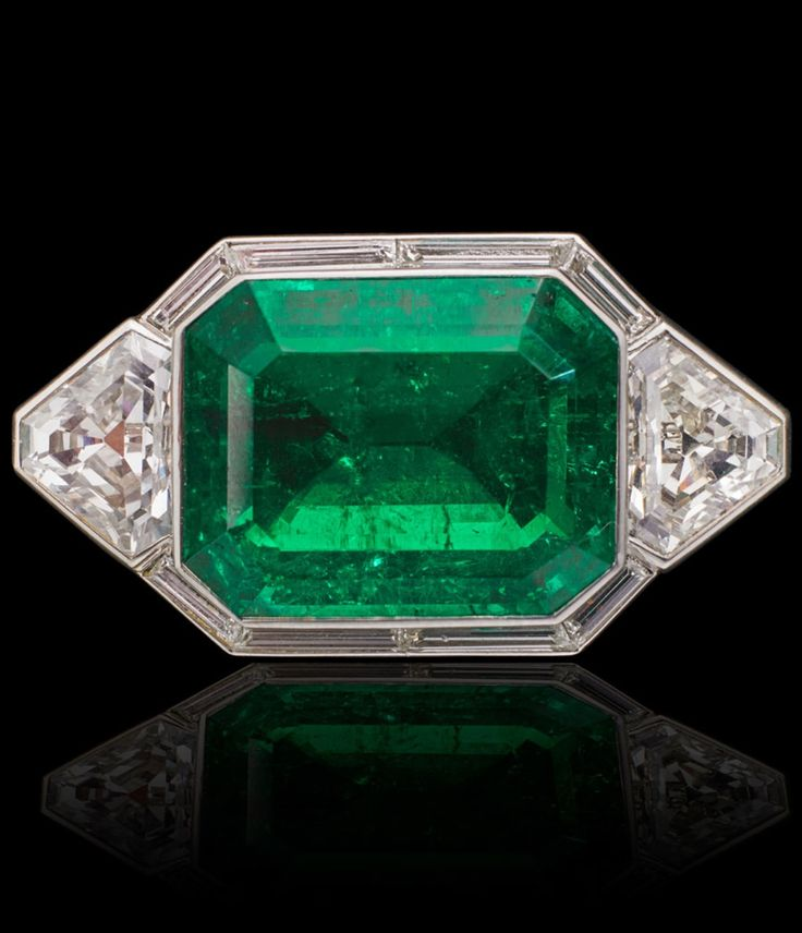 A MAGNIFICENT ART DECO COLOMBIAN EMERALD JEWEL. The rectangular emerald with canted corners, weighing approximately 29 carats, in an Art Deco platinum setting, flanked by a pair of shield shaped diamonds. Unmarked, with hinged bails for vertical pendant wear and detachable fittings for horizontal brooch wear. #ArtDeco #jewel