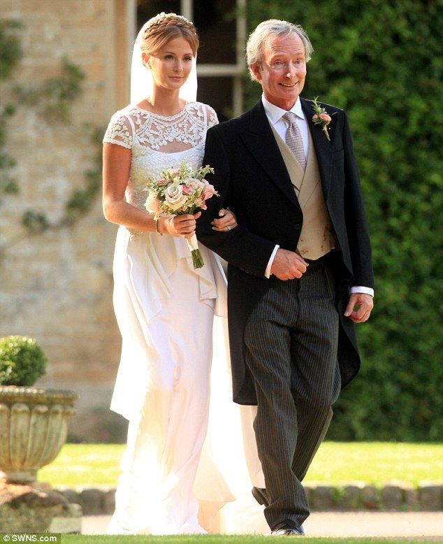 Here comes the bride! Millie looked utterly breathtaking in a vintage white lace wedding dress and Christian Louboutin heels as she made her way down the aisle on the arm of her proud father, Nigel