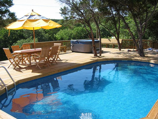 above ground pool + deck with trees.