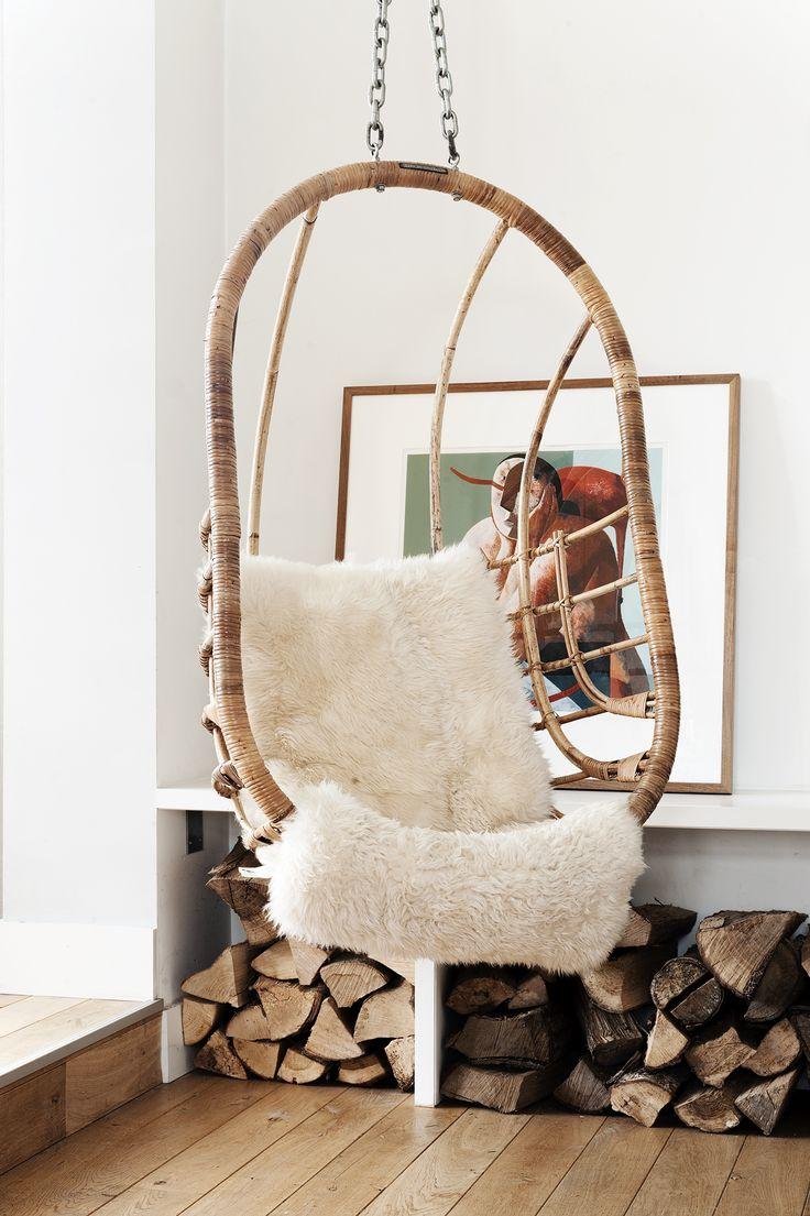 Deze hangstoel, hangend naast de haard, gemaakt van rotan is een fraai detail in het interieur. www.jolandaknook.nl