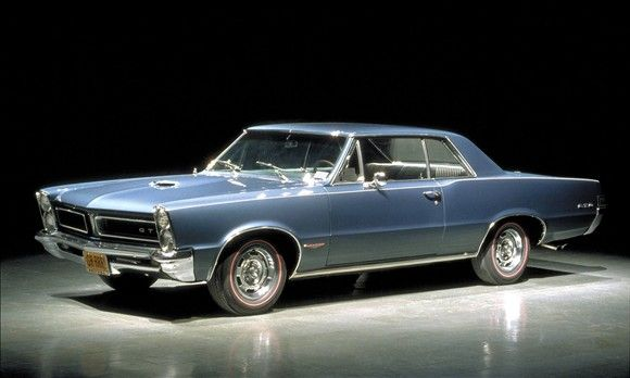 """6. 1965 Pontiac GTO  4,150 votes, 11 percent of the vote The Pontiac GTO, affectionately dubbed the """"Goat,"""" is about as quintessentially muscle car as it gets. For 1965, the 389-cubic-inch engine packed a stout 335 horsepower and was offered with a Tri-Power option good for an additional 25 ponies. While it was capable of dashes to 60 mph in less than six seconds, the GTO's sketchy brakes and subpar steering made the heavy beast quite a handful to control. But hey, that's all part of…"""