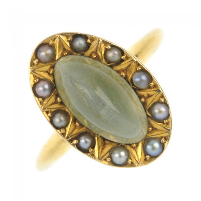 A late 19th century 18ct gold cat's-eye gem and split pearl cluster ring. The oval cat's-eye green gem cabochon, within a split pearl and geometric surround, to the plain band. Weight 4.2gms.