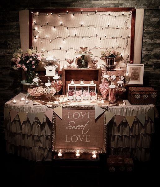Rustic/Vintage Sweets table. Both back corners of table have 2 vintage leather trunks. On L is vintage scale filled with sweets, R holds scrabble letter sign. On R is vintage wire basket which holds take-home bags. Gold frames burlap with stencil letters. Satin in loosely draped across tabletop. Backdrop has a simple frame strung White whites covering mini chickenwire?