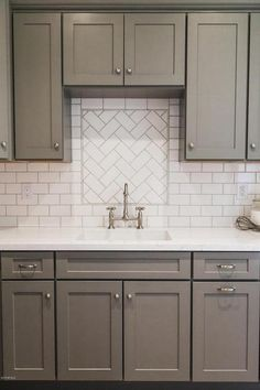 White and gray kitchen features gray shaker cabinets paired with white quartz countertops and a white subway tiled backsplash.