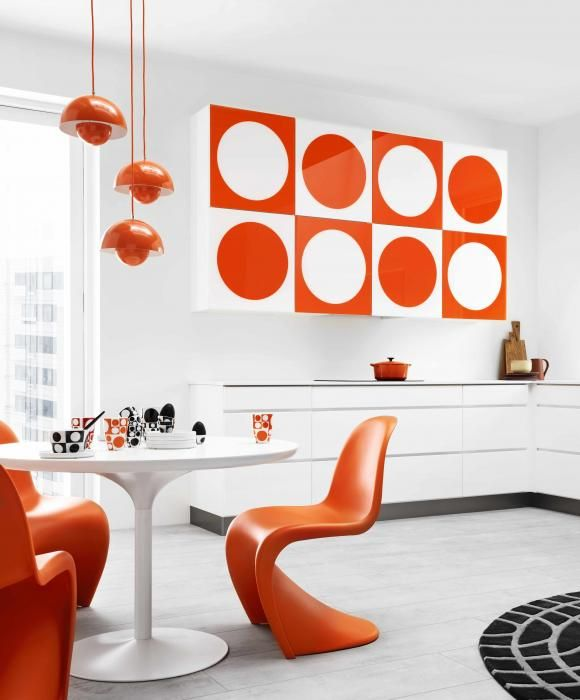 the Panton chairs in orange, with that great pedestal table. I love how the pop art echos the colours and the shapes.