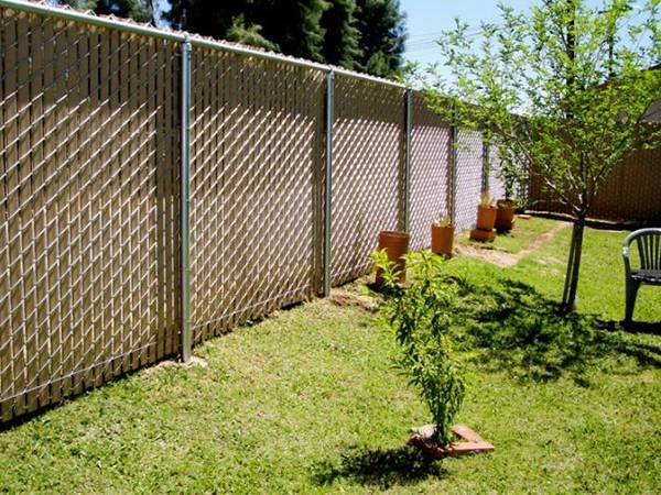 The Chain Link Fence With Slat Is Installed In A Beautiful Garden Backyard Fences Fence Design Backyard