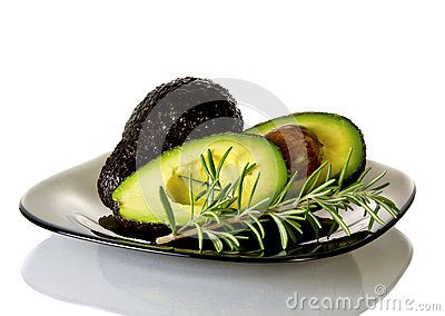 Avocado  cut into pieces and sprig of rosemary   placed on a plate . isolated  background.