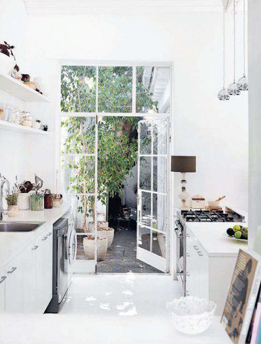 Gravity Interior : White kitchen with doors to the garden