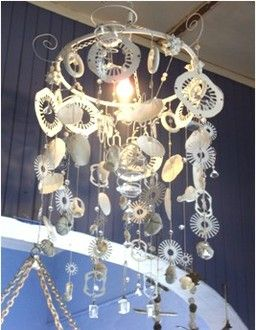 Netball hoop frame  adorned with wire curls, wine glasses, crystals, glass beads, sea-washed glass pieces, white mussel shells, motor components, beach pebbles.