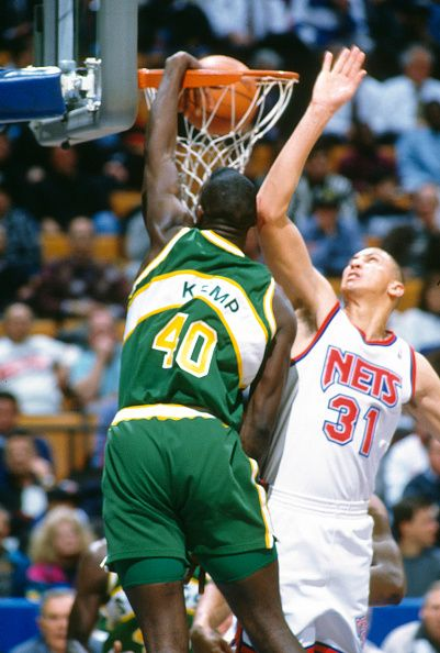 Shawn Kemp of the Seattle Supersonics slam dunks over Sam Bowie of the New Jersey Nets during an NBA basketball game circa 1993 at the Brendan Byrne...