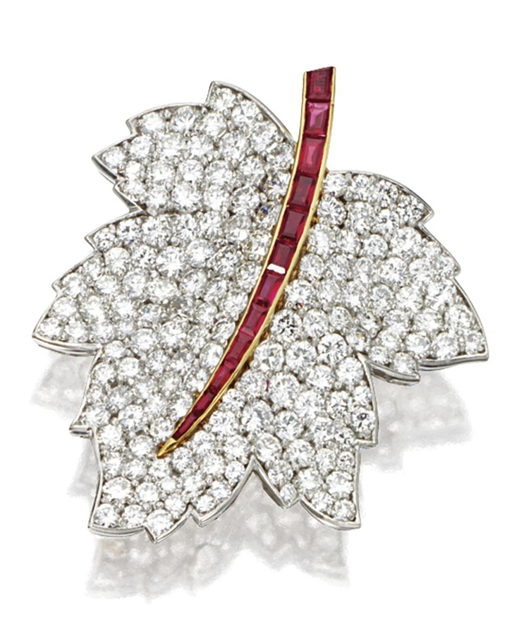DIAMOND AND RUBY MAPLE LEAF BROOCH, VAN CLEEF & ARPELS, NEW YORK, 1967.  Pavé-set with 160 round diamonds weighing 11.37 carats, the stem set with calibré-cut rubies weighing 2.00 carats, mounted in platinum and 18 karat gold, signed Van Cleef & Arpels, numbered N.Y. 38766-1.