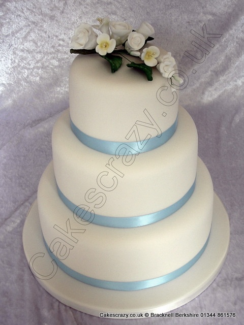 Three tier micro wedding cake from my budget wedding cake selection. Finished with a blue satin ribbon and sugar flower spray for illustrative purposes only. For more details see my budget wedding cakes from the main menu