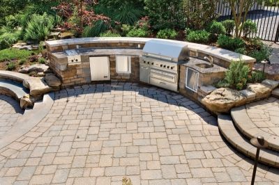 A custom outdoor kitchen with a grill, side burners, beverage refrigerator, sink and storage cabinet was part of this patio installation.