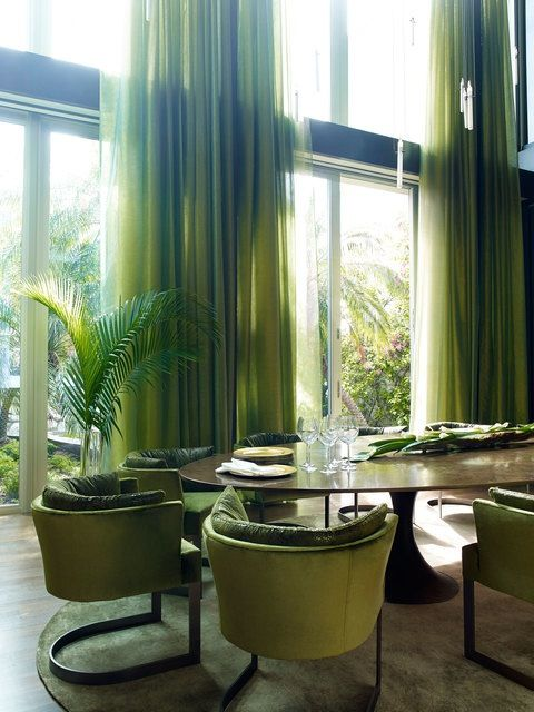 The serene courtyard sets the tone for the formal dining room. The lush vegetation of the garden inspired the rich mossy tones of the velvet covered dining chairs, the sumptuous ombre silk rug and the delicate sheer drapes.