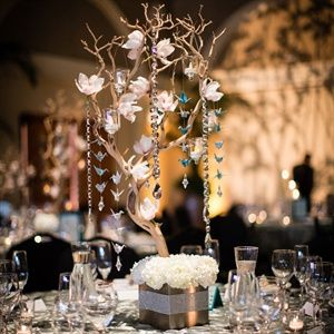 The tree branch centerpieces were decorated with bright white orchids, miniature origami cranes and
