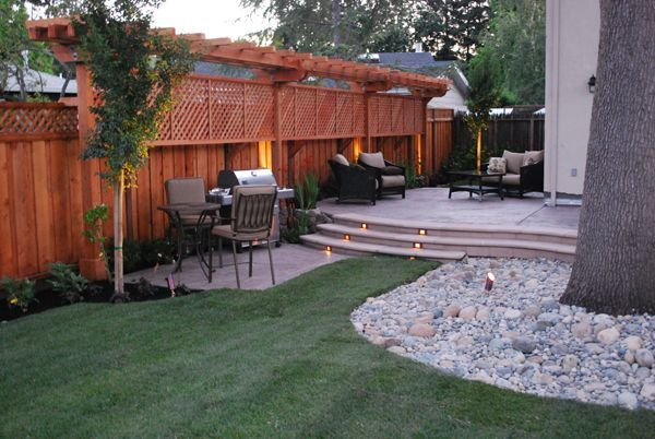 Redwood T-Arbor and Lattice Privacy Screen ~ This entire corner of the backyard is cleverly designed for warm weather outdoor enjoyment. I love the addition of the small bistro table next to the grill yet close enough to the patio as to include the grill master in the merry making. The lighting adds the perfect ambiance to an enjoyable summer gathering.