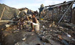 A woman and a child sit on buckets amid the ruins of their home destroyed by Hurricane Matthew, in Jeremie, Haiti, on Monday.