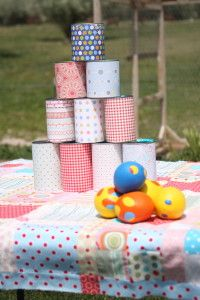 Cans & scrapbooking paper. You'll need 10 cans total.  Set them up in a pyramid shape and provide some balls for the kids to throw at the cans.