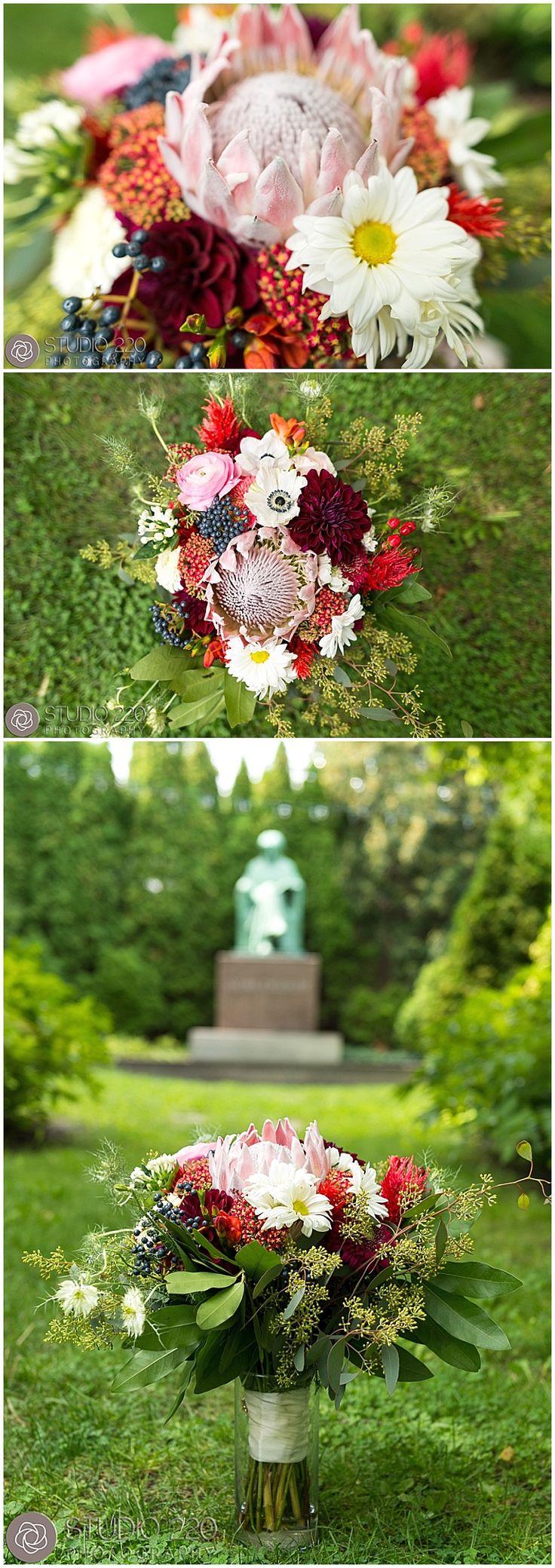 Inside the bouquet: Queen proteas, coxcombs, dahlias, ranunculus, zinnias, anemones, privets, bay leaf, seeded eucalyptus, bouvardias, mums, magnolias, feather celosias, scabiosas, hypericum, and freesia. Designed by Minneapolis wedding florist Artemisia Studios. Photos by Studio 220 (https://www.studio220photography.com/) #bridalbouquet #flowers #floral #wedding #Bouquet #minneapolisweddingflorist #artemisiastudios