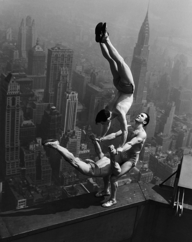 Acrobats Jarley Smith (top), Jewell Waddek (left), and Jimmy Kerrigan(right) perform a delicate balancing act on a ledge of the Empire State Building in New York City. August 21, 1934 Manhattan, New York, New York, USA