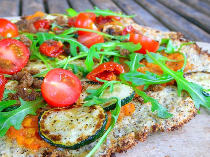 Pizza van bloemkool met gegrilde courgette, rucola en tomaatjes. Dit recept is voor 2 volwassenen Boodschappenlijstje: voor de pizza 450 gram bloemkool in roosjes 65 gram amandelmeel 3 eetlepels ch…
