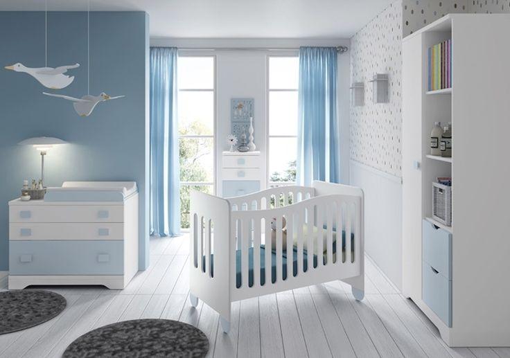La chambre BILBO est dans les tons blanc et ciel avec un berceau, une commode, un matelas à langer, une armoire et un chiffonnier