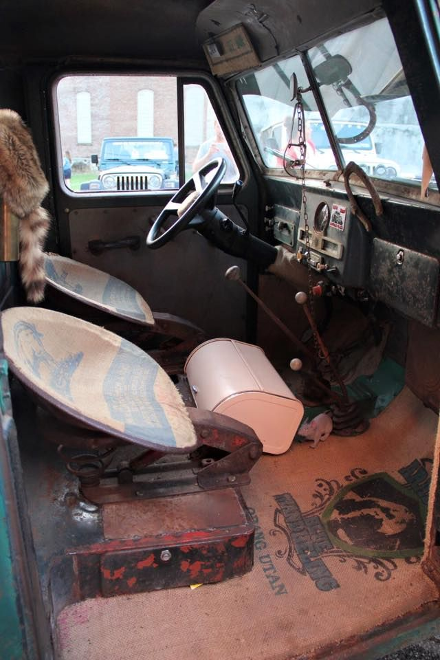 Ratrod interior with some kind of tractor looking seats, canvas floor covering.