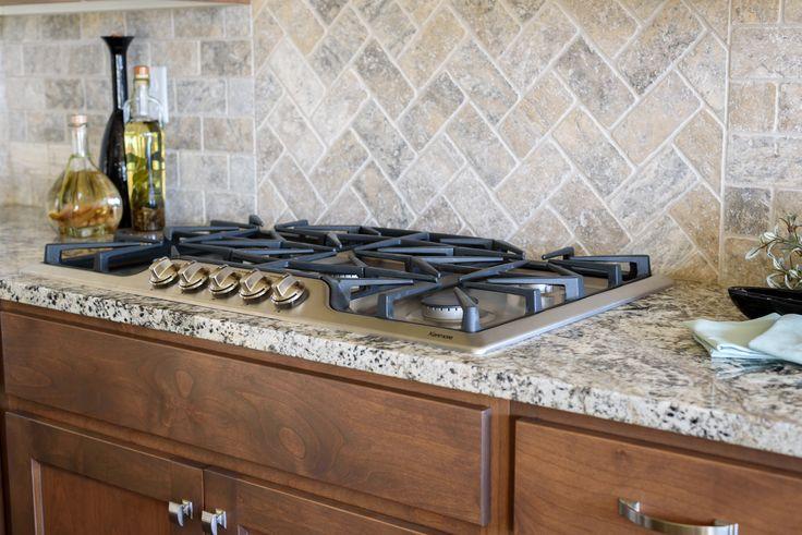 "Full custom Herringbone patterned silver travertine backsplash with a 36"" Kenmore 5 burner cooktop."