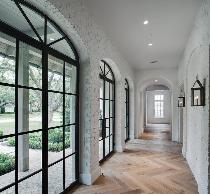 Gorgeous home features a hallway clad in exposed brick painted white fitted with arched steel and glass windows alongside a light wood herringbone floor illuminated by carriage wall sconces.